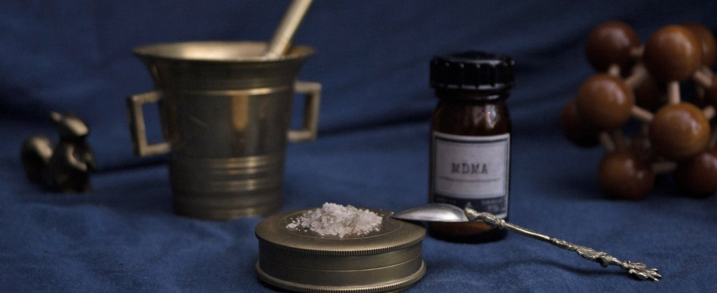 "White powder on a lid with a spoon resting on it. In the background, a mortar and pestle and a bottle labeled ""MDMA."""